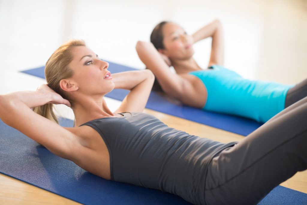 Young woman doing sit-ups while lying on exercise mat at health club