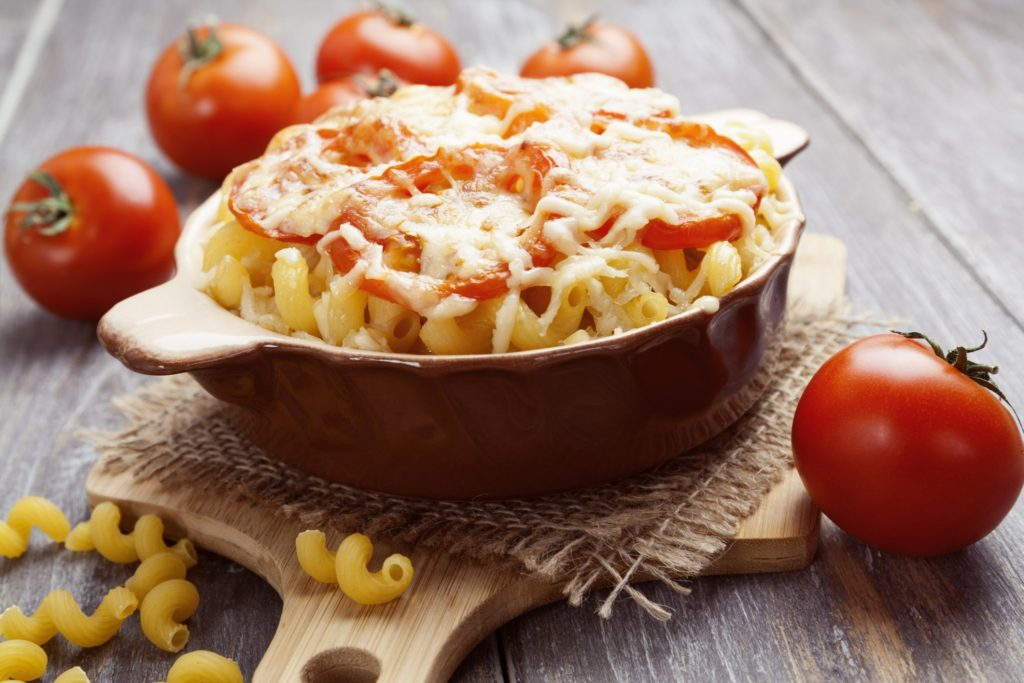 Pasta baked with tomato and cheese in a ceramic pot
