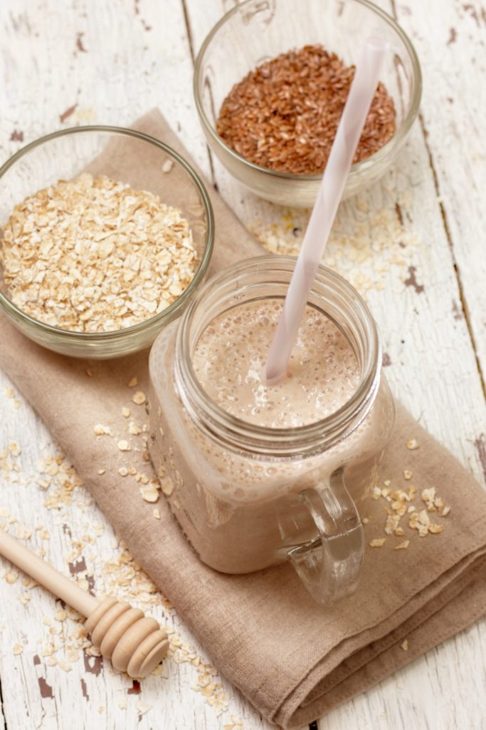 Smoothies with milk (soy, almond, coconut), oatmeal and flax seeds on a wooden background (top view)