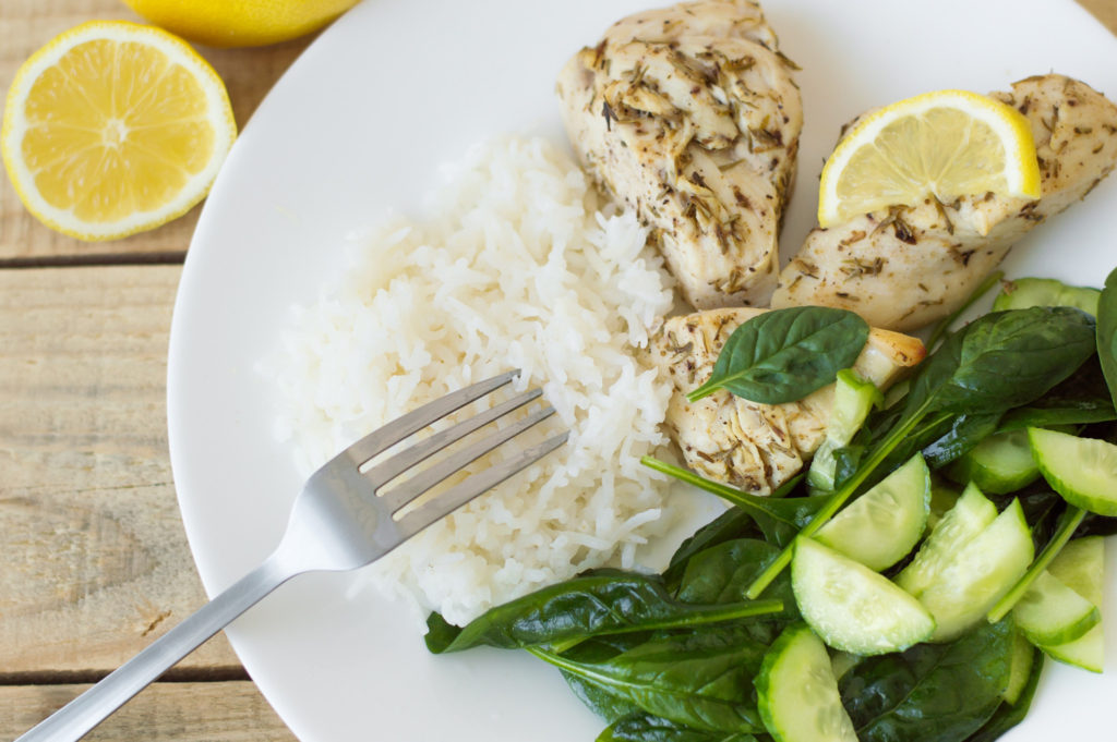 Baked chicken breasts with lemon, white rice and green spinach and cucumber salad