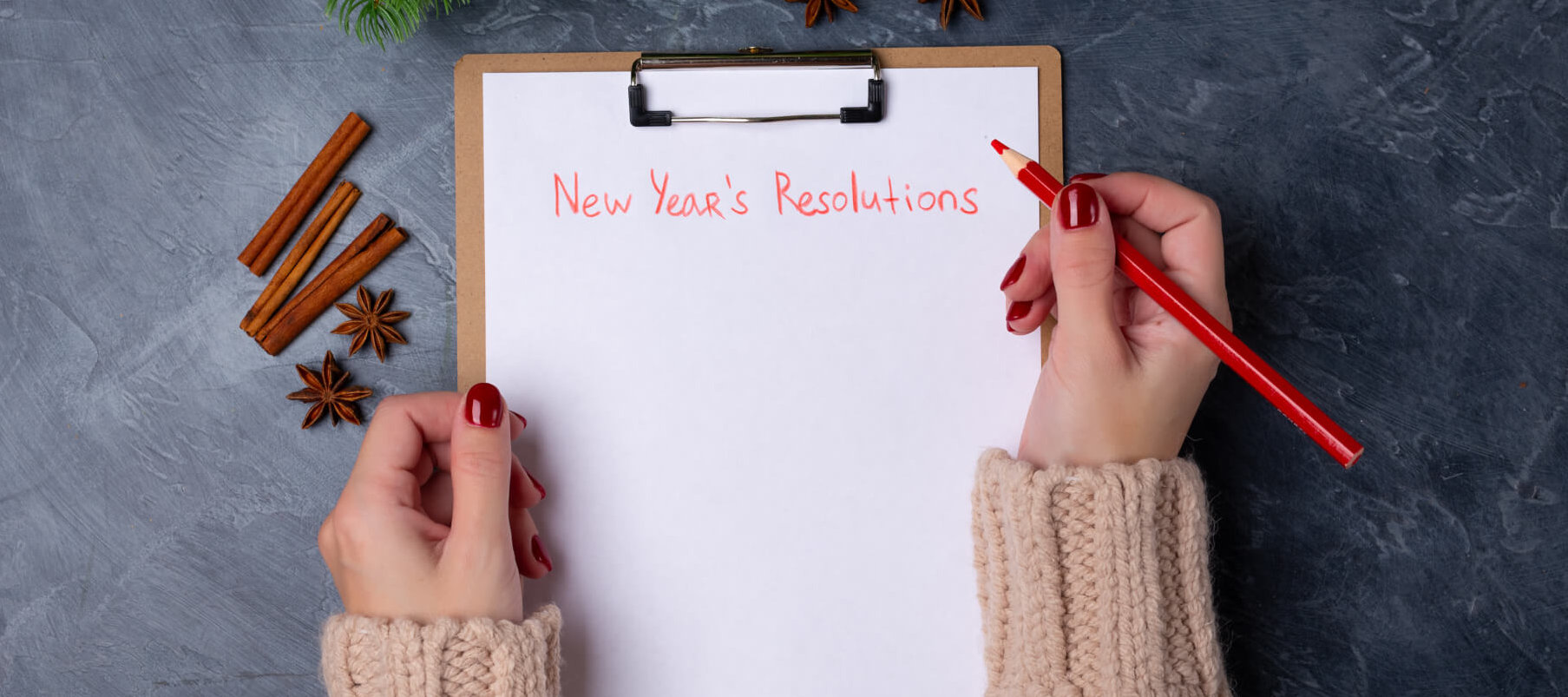Woman hands ready to write new year's resolutions on blank list on dark background. Flat lay. Top view. New year concept. Target success concept. Personal goals.